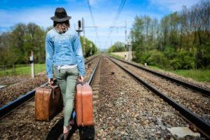 Une jeune femme en quilibre sur des rails avec des valises la main