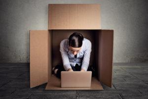 businesswoman introvert sitting in box working on laptop computer